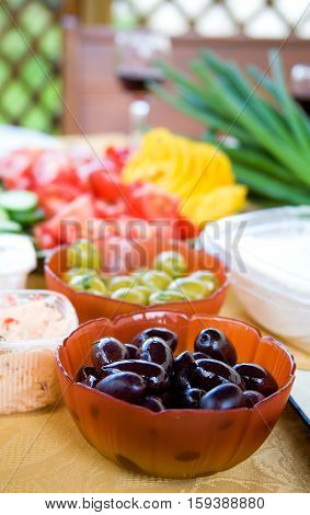 Summer appetizers. Black and green olives and sliced fresh vegetables on a table. Shallow depth of field focus on black olives