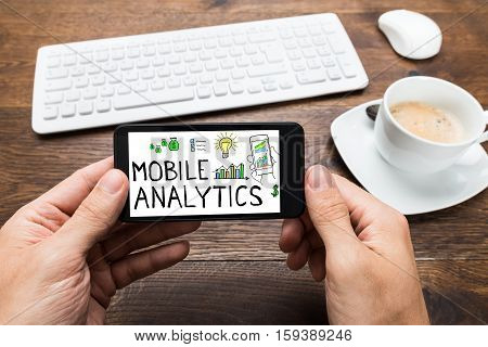 Close-up Of Person Hand Holding Mobilephone Showing Mobile Analytic Concept At Wooden Desk In Office