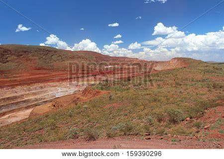 One of the many long strip open cut pits at at Tom Price iron ore mine in the Pilbara region of Western Australia.  Blending in with the natural landscape on either side.