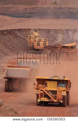 Fully loaded yellow XE-MC haul truck carrying waste rock at the Tom Price iron ore mine in the Pilbara region of Western Australia