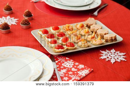 Decorated Christmas Table With Plate Of Tasty Tartlets (cheese, Tomatoes, Seafood And Foie Gras)
