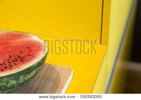 half of a water melon in a yellow kitchen