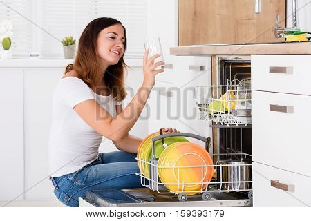 Young Woman Taking Drinking Glass From Dishwasher In Kitchen