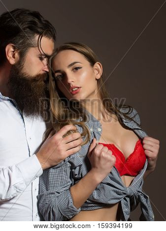 Young loving sexy couple of bearded handsome man hipster with beard and moustache and pretty girl or beautiful woman in red sexi bra in unbutton shirt on grey wall