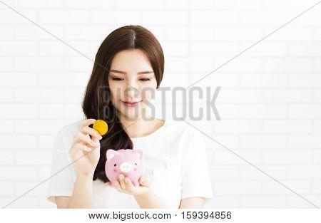 smiling young beautiful asian woman with piggybank