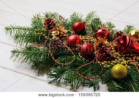 Christmas swag with red ornaments golden beads and pine cones. Christmas table centerpiece with golden decor.
