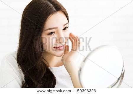 Happy young asian woman looking on mirror