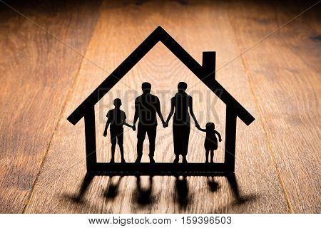Silhouette Of House With Family Cutout On Wooden Desk