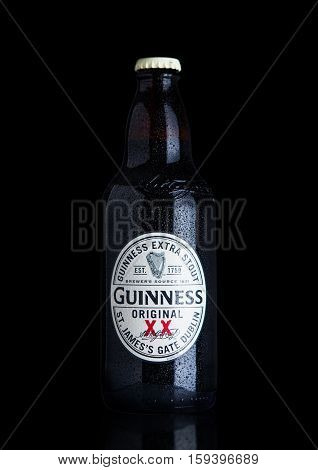 LONDON UK - NOVEMBER 29 2016: Guinness extra stout beer bottle on black background. Guinness beer has been produced since 1759 in Dublin Ireland.
