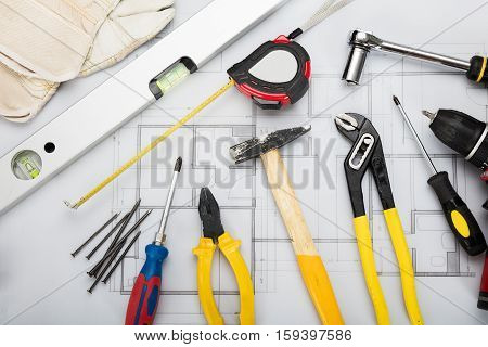High Angle View Of Working Tools On Blueprint On Office Desk