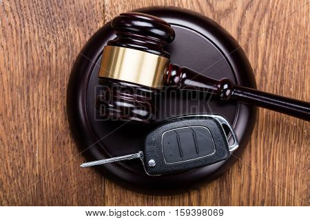 Car Key On Judges Gavel At Wooden Desk In Courtroom