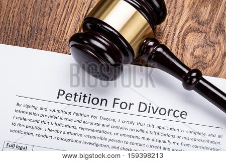 Wooden Gavel On Petition For Divorce Paper At Wooden Desk In Courtroom