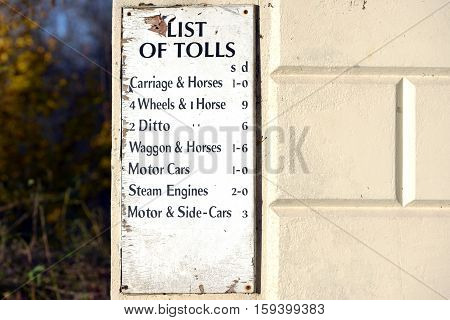 Old white sign showing toll road prices.