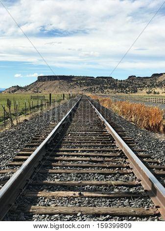 Railroad tracks run along farmland in Crook County in Central Oregon on a fall afternoon.