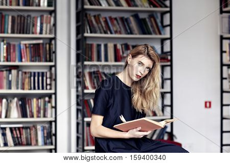 Beautiful blonde woman with a book in a public library. Red lips, long white hair