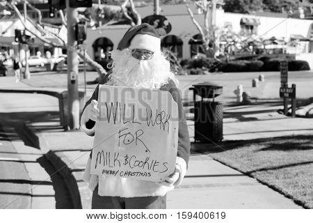 Santa Claus stands on the street with a  Will Work for Milk and Cookie cardboard sign. Homeless Santa with sign. Will Work for food. black and white