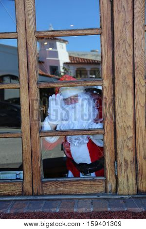Santa Claus looks out a window.