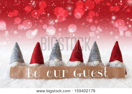 Label With English Text Be Our Guest. Christmas Greeting Card With Red Gnomes. Sparkling Bokeh And Christmassy Background With Snow And Stars.
