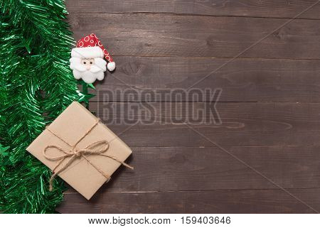 Gift Box And Santa Claus Are On The Wooden Background With Empty Space For Christmas Day