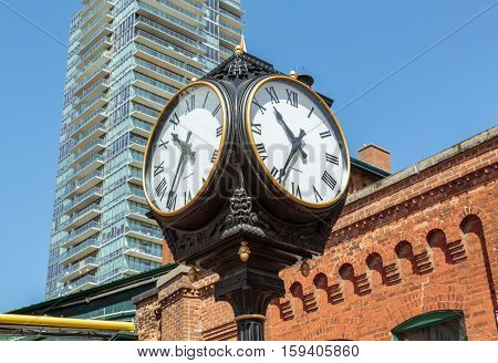Toronto city, Ontario, Canada, May 22, 2016, Toronto city landscape view with vintage classic clocks standing against brick building at Toronto distillery historic district square