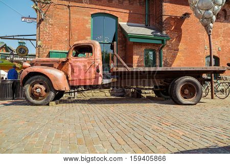 Toronto city, Ontario, Canada, May 22, 2016, old vintage classic retro truck parked against brick building at Toronto distillery historic district