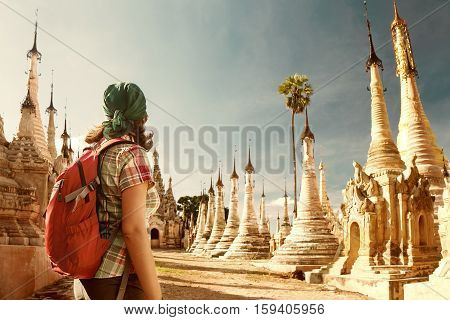 Backpacker traveling with backpack and looks at Buddhist stupas