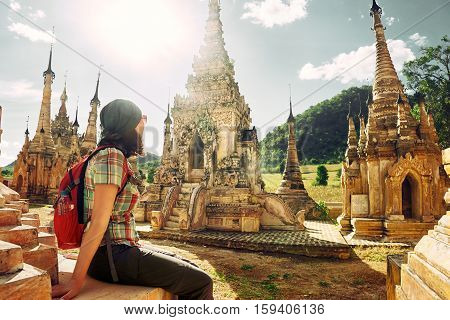 Young traveller enjoying a looking at Buddhist stupas. Burma Asia. Traveling along Asia active lifestyle concept.