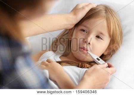 Woman measuring temperature of small sick girl