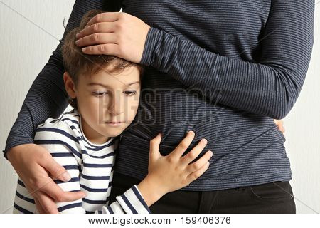 Mother hugging sad little boy, close up view