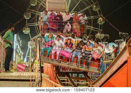 HOWRAH WEST BENGAL INDIA - MARCH 1ST MARCH 2015 : Young people enjoying Roller coster ride at Howrah West Bengal India. Shot at night with colored lights.