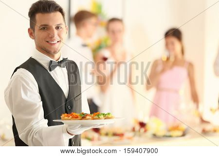 Handsome young waiter with plate full of tasty tartlets at party