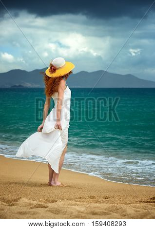 Lonely woman in a white dress standing at the sea shore and watching the storm