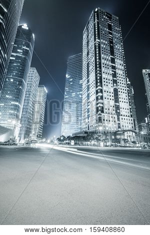 futuristic office buildings at night and city road with blue tone in shanghai