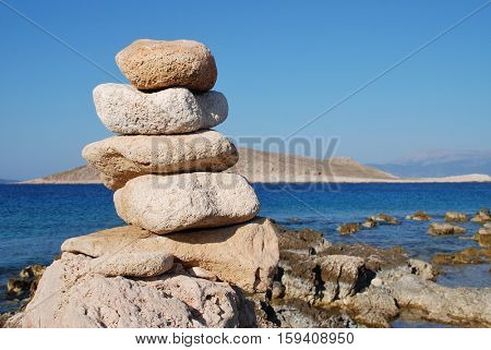 A tower of stones on Ftenagia beach at Emborio on the Greek island of Halki. The uninhabited island of Nissos is in the background.
