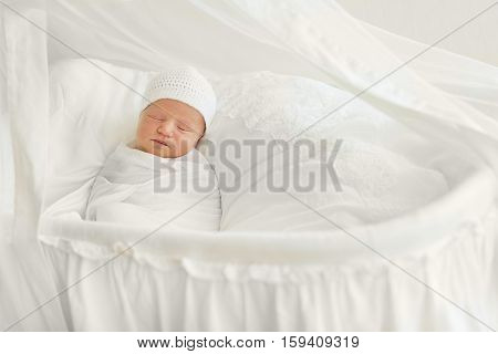 Newborn baby 7 days wrapped in white diaper and hat and sleeping peacefully in the cradle. Clean and disinfection care of the child
