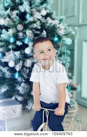 Fun boy 3 years old playing in the room decorated for the Christmas tree. Beautiful Christmas interior in white and blue colours happy kid waiting for presents