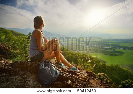 A girl sits on the edge of the cliff and looking at the sun valley and mountains.