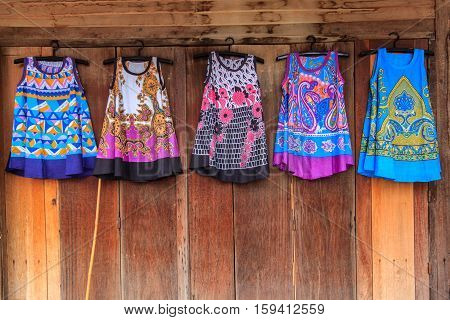 Colorful traditional costume southeast asia on old wooden background in Thailand market