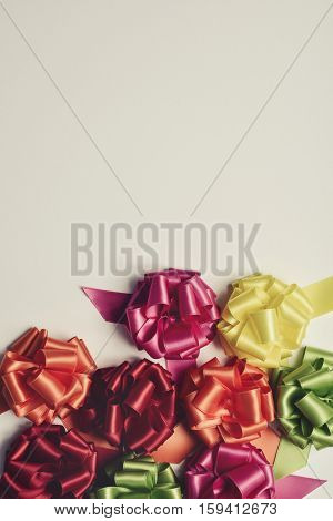 some satin gift ribbon bows of different colors on an off-white background, with a negative space and a retro effect