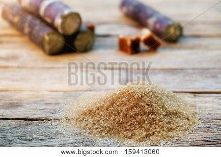 brown cane sugar with sugarcane on wooden background soft focusselective focus.
