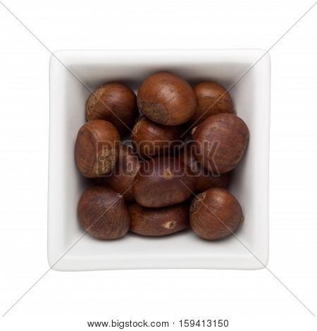 Roasted chestnuts in a square bowl isolated on white background