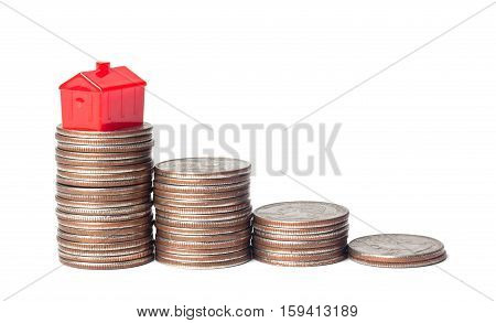 Toys house and pile of coins representing financial goal of home ownership