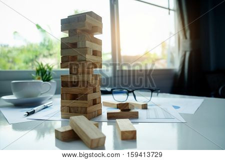 Planning risk and strategy in business concept businessman gambling placing wooden block on a tower with meeting background.vintage tone Retro filter effectsoft focuslow light.(selective focus)