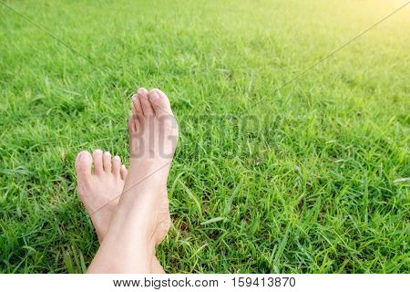 Feet of asian woman relaxing on a sofa and looking outside a green background view at home terrace. Relaxing concept.