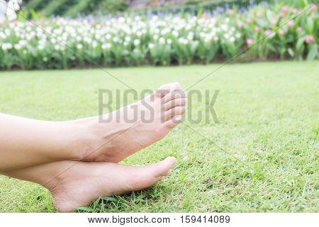 Feet of asian woman relaxing on grass field. Relaxing concept.