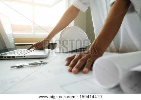 Hands of engineer working with computer and pointing on blueprint with engineering tools on desk. Construction concept. Vintage tone retro filter effectsoft focus(selective focus)