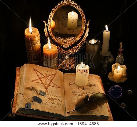 Mystic still life with black magic book and mirror in candle light. Halloween concept, scary ritual or spell with occult and esoteric symbols, divination rite. Vintage objects on table. There is no foreign text in the image, all symbols are imaginary and