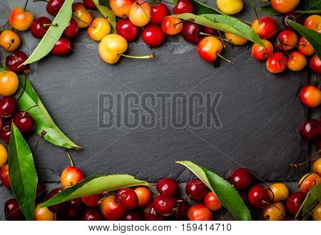 Ripe red and yellow cherry with leaves on black background. Frame with free space for tex. Stone slate plate, copy space. Top view