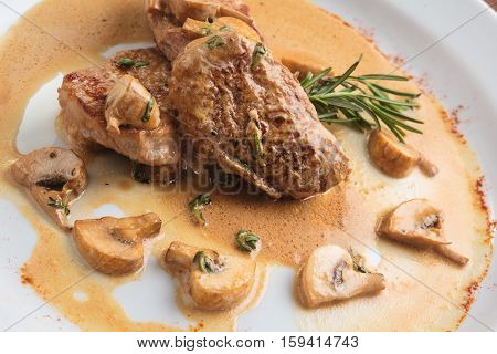 Concept: restaurant menus healthy eating homemade gourmands gluttony. White plate of pork medallions with mushroom sauce on weathered wooden table. poster