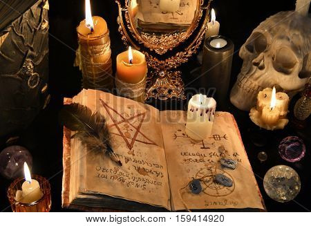 Mystic background with old book, skull, candles and mirror.  Halloween concept, black magic ritual or spell with occult and esoteric symbols, divination rite. Vintage objects on table.
